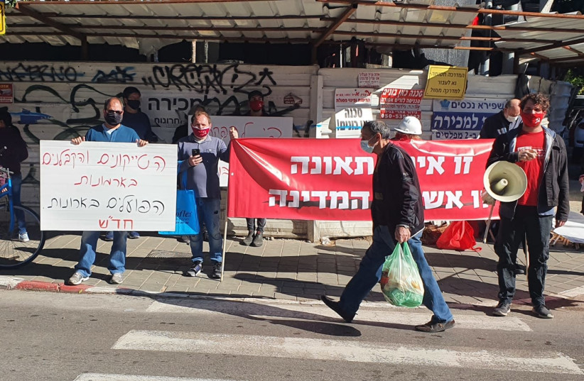 "Hadash party activists hold banners with the captions ""Tycoons and building contractors live in palaces while workers get coffins"" and ""It is not an accident, it is the fault of the state.""    (photo credit: Courtesy)"