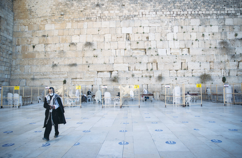 A MAN walks away from the Western Wall earlier this month. (photo credit: YONATAN SINDEL/FLASH 90)