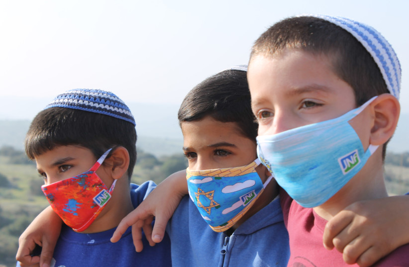 PUPILS OF the Gevim School in Beersheba wear masks designed by British schoolchildren.  (photo credit: Courtesy)