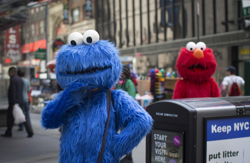 Characters dressed up as the Cookie Monster and Elmo from Sesame Street stand in Times Square while waiting to pose for photographs with people for tips (photo credit: SHANNON STAPLETON/ REUTERS)