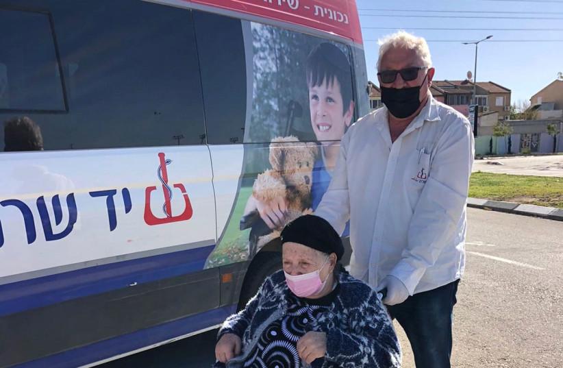 A Yad Sarah volunteer helps a Holocaust survivor to reach a vaccination center. (photo credit: COURTESY YAD SARAH)