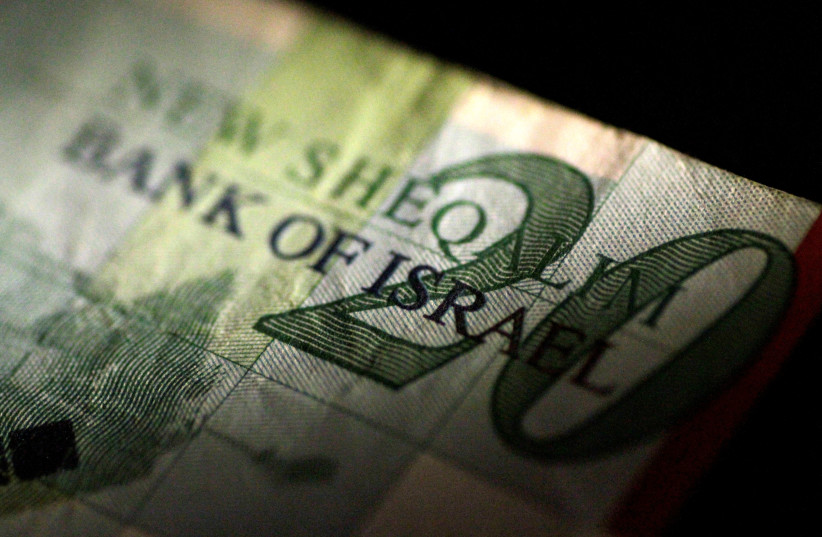An Israeli shekel note is seen in this June 22, 2017 illustration photo.  (photo credit: REUTERS/THOMAS WHITE/ILLUSTRATION/FILE PHOTO)
