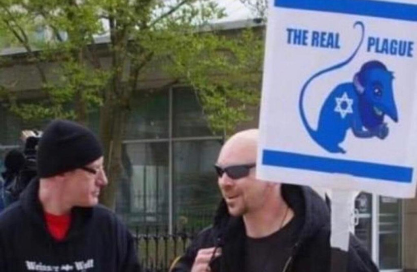 A picture posted on Twitter shows a man holding an anti-Semitic poster.  (photo credit: COURTESY TEL AVIV UNIVERSITY)