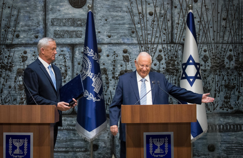 Israeli president Reuven Rivlin presents Blue and White party leader Benny Gantz with the mandate to form a new Israeli government, after PM Netanyahu's failure to form one, at the President's Residence in Jerusalem on October 23, 2019.  (photo credit: YONATAN SINDEL/FLASH 90)