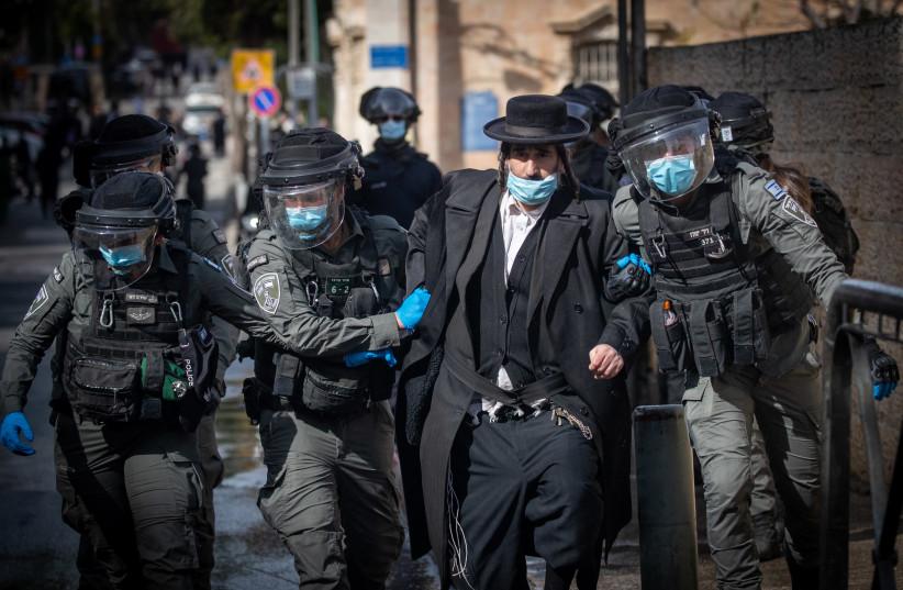 Israeli police officers clash with ultra-Orthodox Jewish men during enforcement of coronavirus emergency regulations, Jerusalem, January 26, 2021 (photo credit: YONATAN SINDEL/FLASH90)