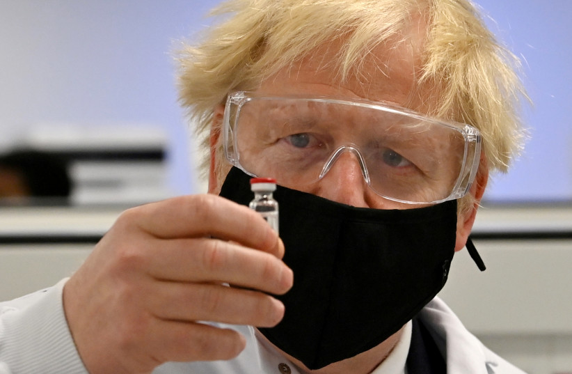 Britain's Prime Minister Boris Johnson poses for a photograph with a vial of the AstraZeneca/Oxford University COVID-19 candidate vaccine, known as AZD1222, at Wockhardt's pharmaceutical manufacturing facility in Wrexham, Wales, Britain November 30, 2020. (photo credit: PAUL ELLIS/ REUTERS)
