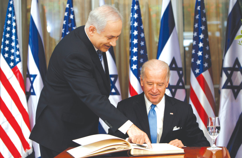 PRIME MINISTER Benjamin Netanyahu shows then-vice president Joe Biden where to sign the guest book, at the Prime Minister's Residence in Jerusalem in 2010. (photo credit: RONEN ZVULUN/REUTERS)
