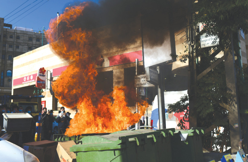 ULTRA-ORTHODOX RIOTERS in Bnei Brak torch a dumpster on Sunday to protest a lockdown ordered because of the COVID-19 pandemic. (photo credit: TOMER NEUBERG/FLASH90)