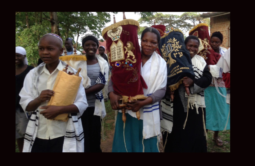 Women and children carry Torah scrolls from an old synagogue building to a new building in Nabagoye, Ugandaz (photo credit: COURTESY BE'CHOL LASHON)