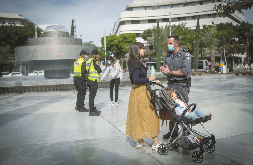 POLICE OFFICERS try to convince passersby to abide by pandemic-related restrictions, in Tel Aviv's Dizengoff Square on Monday. (photo credit: MIRIAM ALSTER/FLASH90)