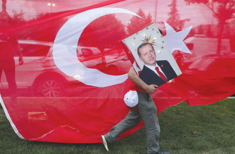 A SUPPORTER of Turkish President Recep Tayyip Erdogan holds his picture in front of Turkey's flag at the ruling AK Party headquarters in Istanbul. (photo credit: GORAN TOMASEVIC/REUTERS)