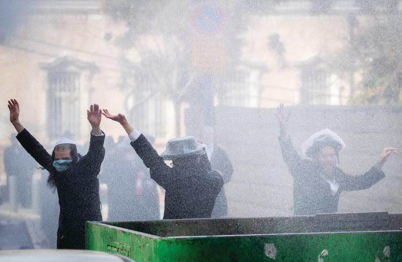POLICE OFFICERS clash with haredim in Jerusalem this week during the enforcement of coronavirus emergency regulations. (photo credit: YONATAN SINDEL/FLASH 90)