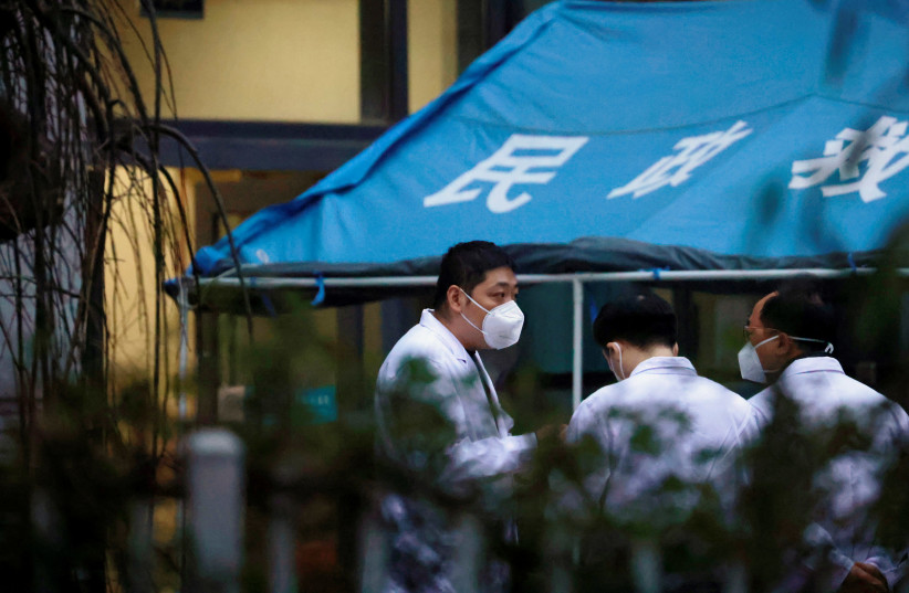 WHO team member at a hospital in Wuhan (photo credit: REUTERS)
