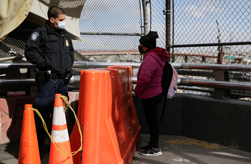 A migrant from Guatemala talk to a US Customs and Border Protection (CBP) agent at the Paso del Norte international border bridge to request asylum in El Paso, Texas, U.S., in Ciudad Juarez, Mexico January 26, 2021.  (photo credit: REUTERS/JOSE LUIS GONZALEZ)