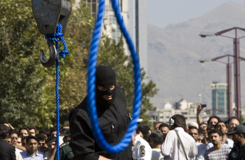 An Iranian policeman takes out his gun ahead of a hanging. (photo credit: REUTERS/RAHEB HOMAVANDI)