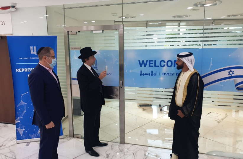 Mezuzah being placed on the representative office of the Israel Diamond Exchange in Dubai.  (photo credit: Courtesy)