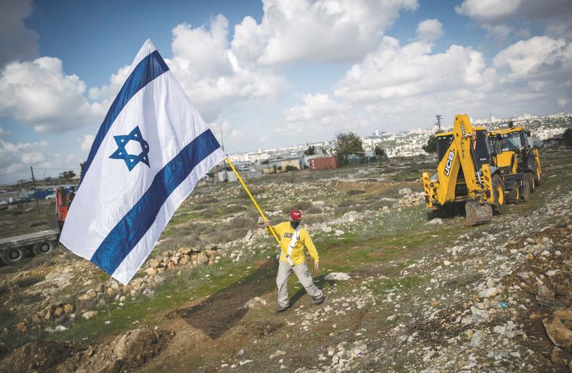 A MAN carrying an Israeli flag walks in Jerusalem's Givat HaMatos neighborhood in November. (photo credit: YONATAN SINDEL/FLASH 90)