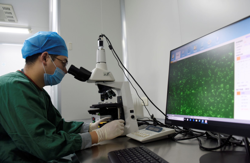 A technician inspects through a microscope a semen sample at a human sperm bank inside a hospital in Hefei, Anhui province, China February 21, 2019.  (photo credit: REUTERS/STRINGER)