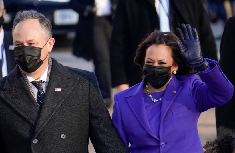 US Vice President Kamala Harris and her husband Douglas Emhoff salute as they walk during the Inauguration Day parade, on January 20.  (photo credit: ERIN SCOTT/REUTERS)