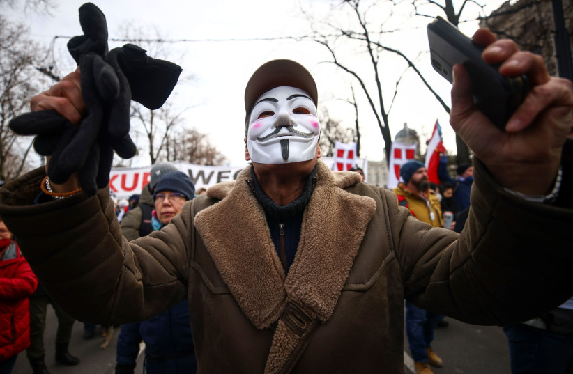 A man wearing a mask gestures during a demonstration against the coronavirus disease (COVID-19) measures and their economic consequences in Vienna, Austria, January 31, 2021. (photo credit: LISI NIESNER/ REUTERS)