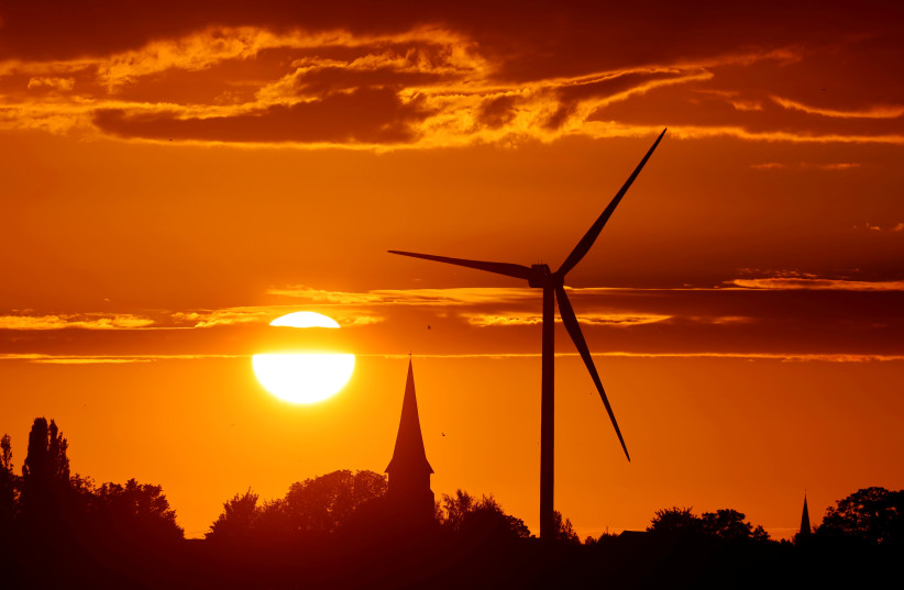 A power-generating windmill turbine is pictured during sunset at a renewable energy park in Ecoust-Saint-Mein, France (photo credit: PASCAL ROSSIGNOL/REUTERS)