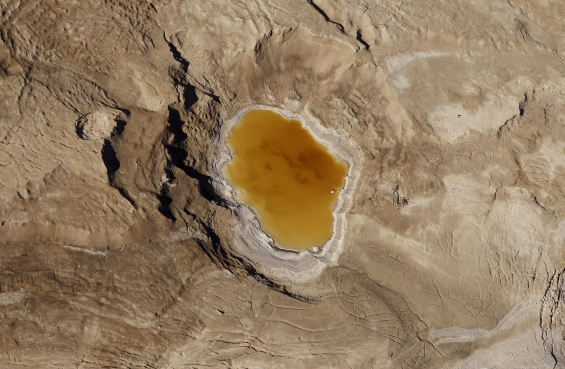 A sink hole filled with water is seen in this aerial view of the Dead Sea December 5, 2011.  (photo credit: BAZ RATNER/REUTERS)