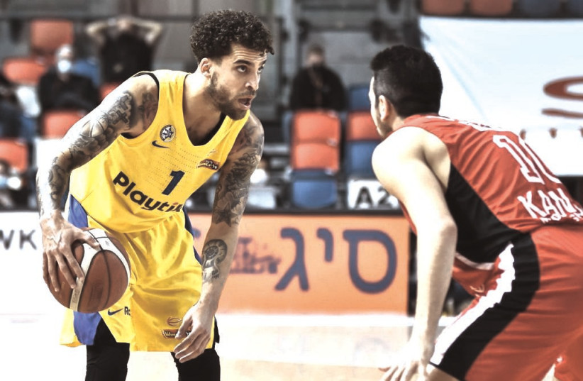 MACCABI TEL AVIV Scottie Wilbekin sizes up the Hapoel Tel Aviv defense during Sunday night's Winner League derby at the Drive-In Arena. The 27-year-old point guard scored a game-high 23 points in Maccabi's 85-69 conquest  (photo credit: DOV HALICKMAN PHOTOGRAPHY)