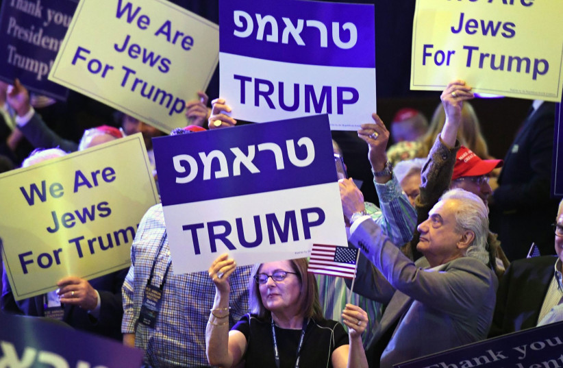 Attendees at the Republican Jewish Coalition's annual leadership meeting hold up signs while waiting to see President Donald Trump speak at The Venetian Las Vegas (photo credit: GABE FRIEDMAN (JTA))