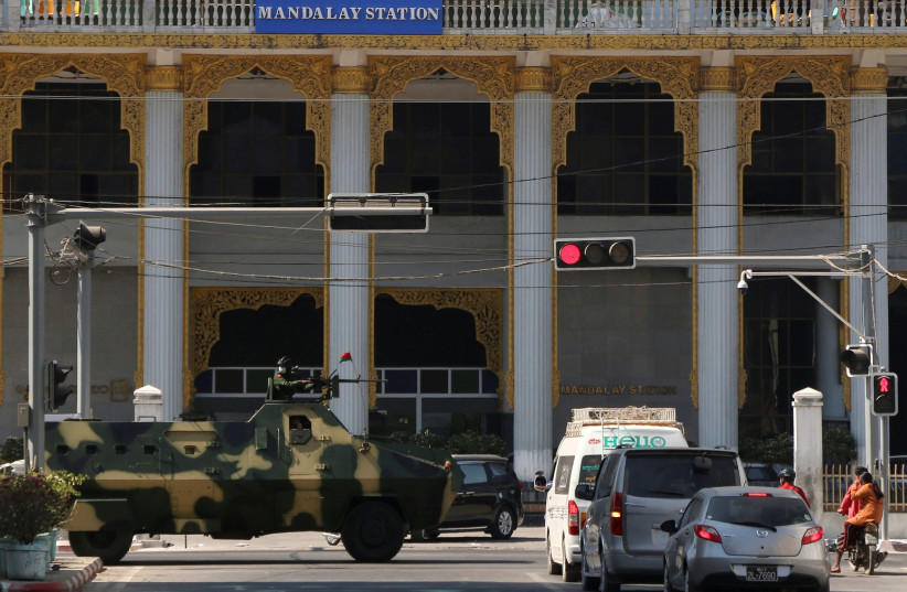 Myanmar army armoured vehicles drive past a street after they seized power in a coup in Mandalay (photo credit: REUTERS/STRINGER)