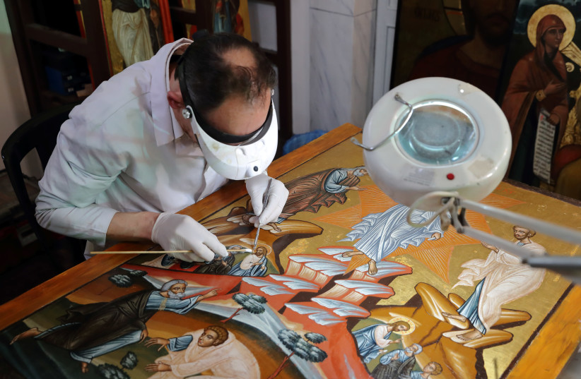 Venizelos Gavrilakis, a senior restorer and conservator from Thessaloniki, Greece, works to clean and restore a 16th century Byzantine Christian icon at a Greek Orthodox church where he set up his laboratory in Istanbul, Turkey January 26, 2021 (photo credit: REUTERS)