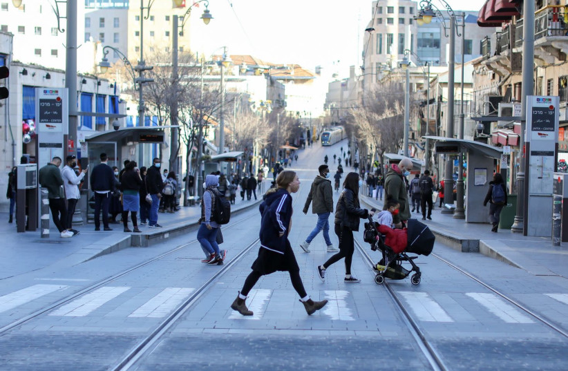 Israelis are seen along the light rail tracks on Jaffa Street in Jerusalem amid the coronavirus pandemic, on February 3, 2021. (photo credit: MARC ISRAEL SELLEM/THE JERUSALEM POST)