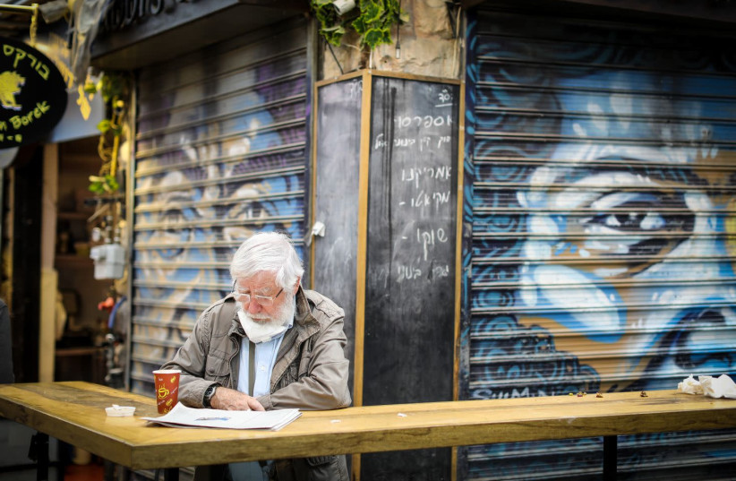 An eldery man is seen sitting alone with coffee and a newspaper at Jerusalem's Mahane Yehuda market amid the coronavirus pandemic, on February 2, 2021. (photo credit: MARC ISRAEL SELLEM/THE JERUSALEM POST)