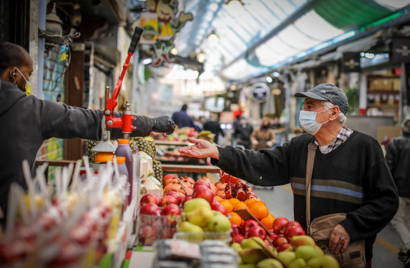 A man is seen at a produce stand at Jerusalem's Mahane Yehuda market during Israel's third lockdown. (photo credit: MARC ISRAEL SELLEM/THE JERUSALEM POST)