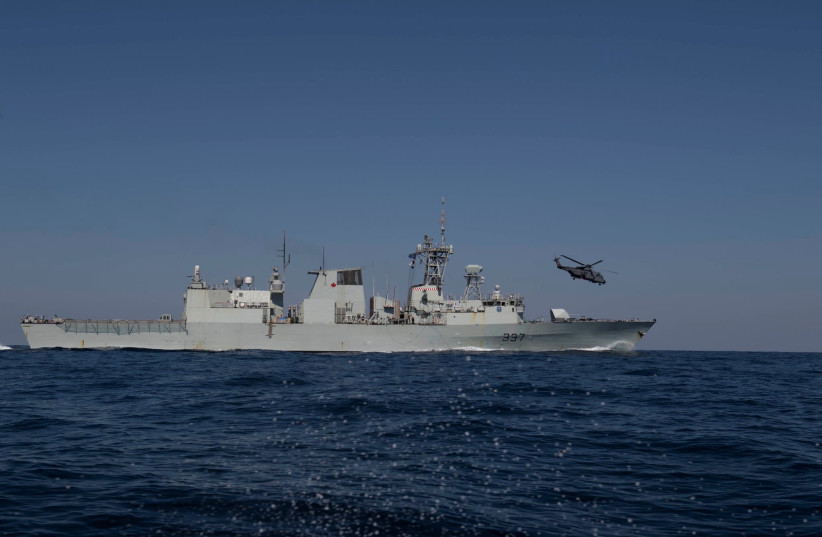 HMCS Fredericton and a helicopter take part in Operation Reassurance at sea (photo credit: REUTERS)