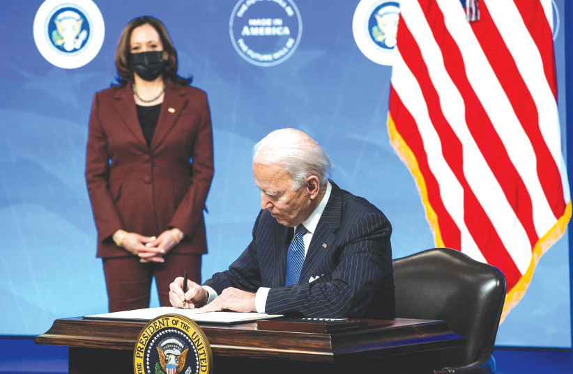US PRESIDENT Joe Biden signs an executive order as Vice President Kamala Harris watches, at the White House in Washington, DC, on January 25. (photo credit: KEVIN LAMARQUE/REUTERS)