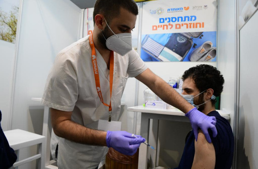 Israelis receive the coronavirus vaccine in Tel Aviv after the Health Ministry announced that anyone over the age of 16 can now be vaccinated, Feb. 4, 2021. (photo credit: AVSHALOM SASSONI/MAARIV)