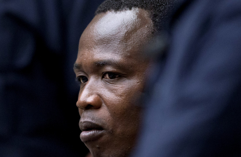 Dominic Ongwen, a senior commander in the Lord's Resistance Army, whose fugitive leader Kony is one of the world's most-wanted war crimes suspects, is flanked by two security guards as he sits in the court room of the International Court in The Hague, Netherlands, December 6, 2016.  (photo credit: PETER DEJONG/REUTERS)