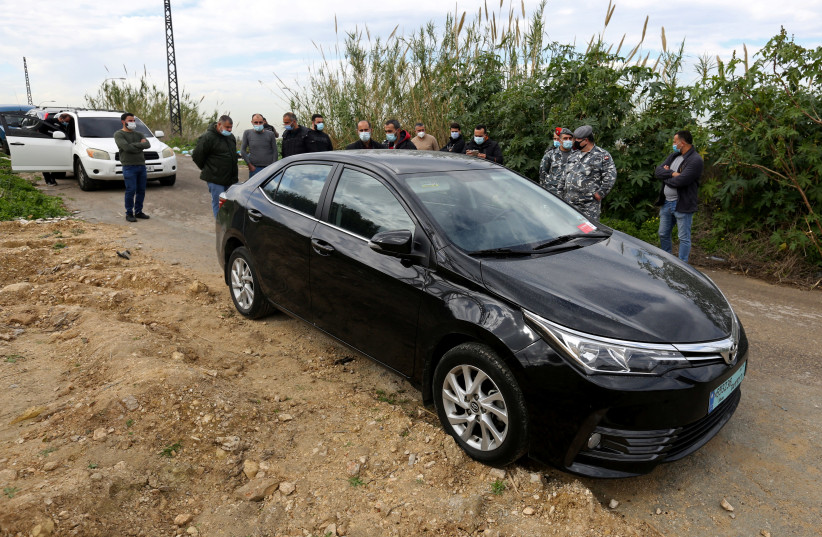 People gather near the car in which Lokman Slim, a prominent Lebanese Shi'ite critic of Iran-backed Hezbollah was found killed, in southern Lebanon, February 4, 2021. (photo credit: AZIZ TAHER/REUTERS)