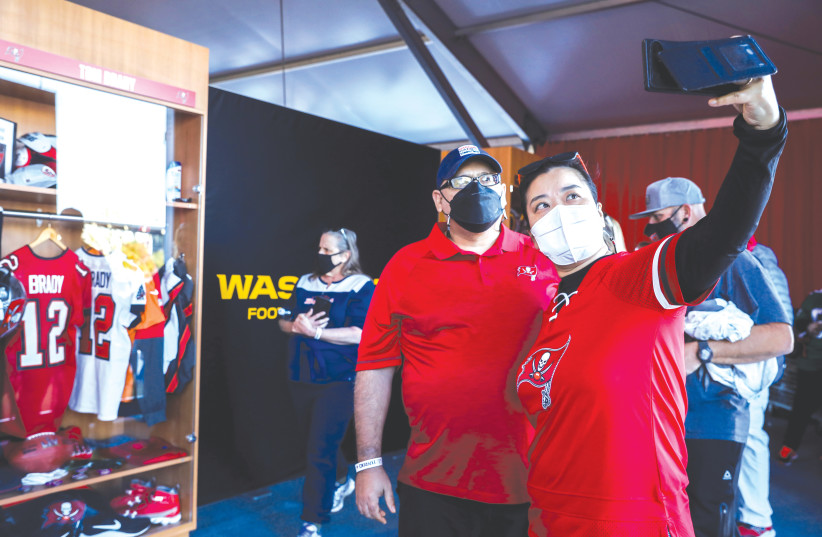 TAMPA BAY BUCCANEERS fans pose for a photo in front of a recreation of Tom Brady's locker at the gallery at The Super Bowl Experience Presented By Lowe's event in Tampa Bay, Florida, earlier this week. (photo credit: EVE EDELHEIT/REUTERS)