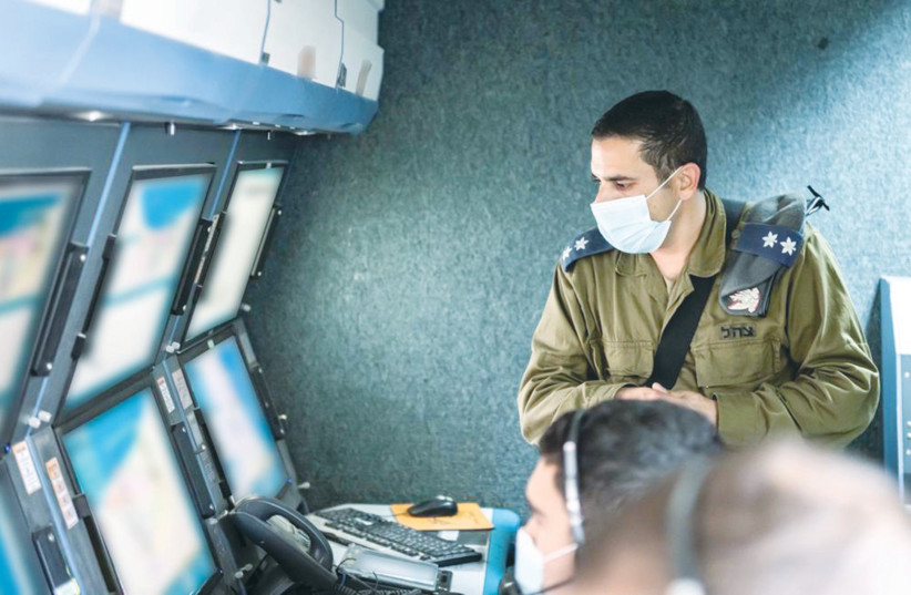 LT.-COL. YEHONATAN supervises soldiers monitoring the screens in the war room at a military post near the Gaza Strip, this week. (photo credit: IDF)