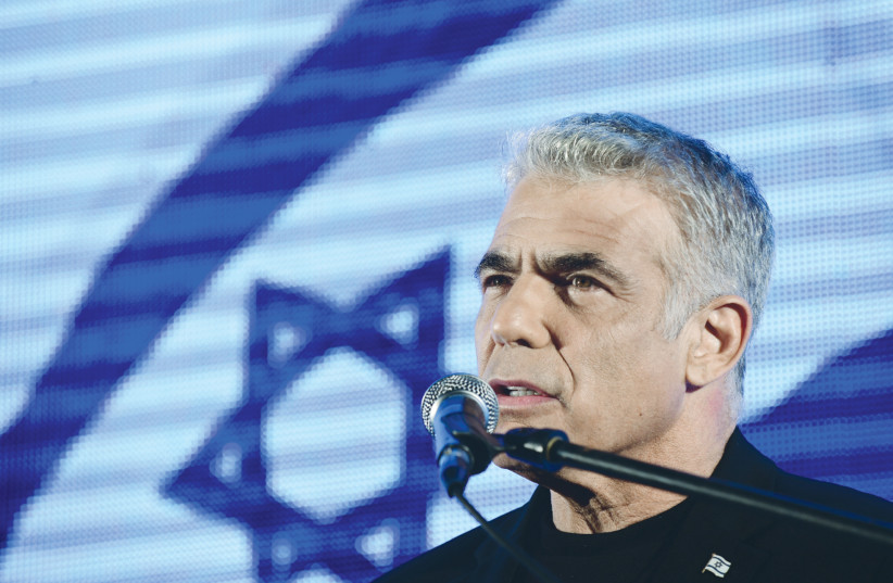 YESH ATID leader Yair Lapid speaks during a protest against Prime Minister Benjamin Netanyahu last year at Rabin Square in Tel Aviv.  (photo credit: TOMER NEUBERG/FLASH90)