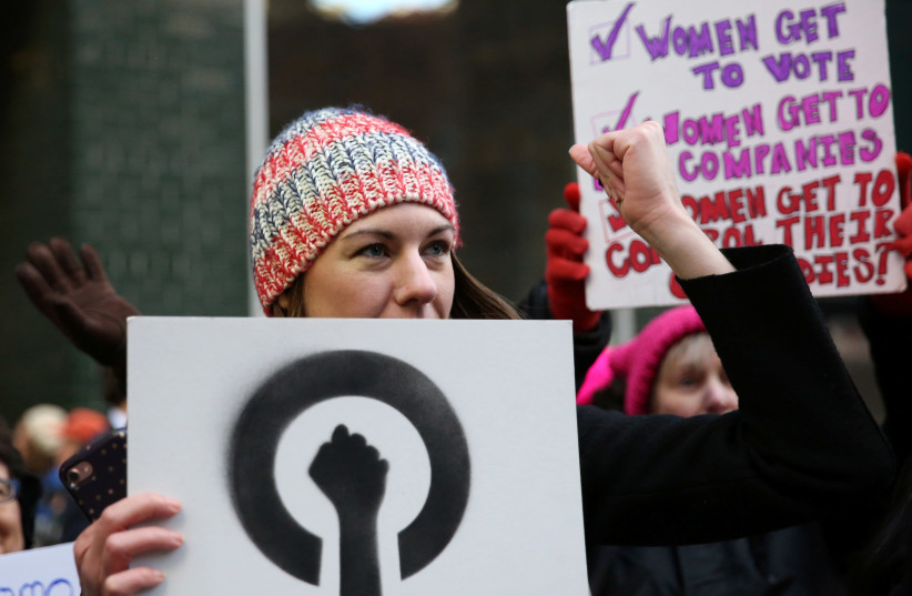 Amy Bettys, co-chair of the Women's Health and Reproductive Rights organization, raises her fist during a chant outside of New York Governor Andrew Cuomo's office in support of the Reproductive Health Act during a Reproductive Rights rally in the Manhattan borough of New York, US, March 22, 2017.  (photo credit: REUTERS/ASHLEE ESPINAL)