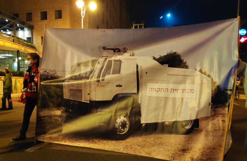 """Anti-Netanyahu protesters in Jerusalem addressed police brutality by erecting a large poster showcasing a water cannon vehicle usually used by police to disperse protests alongside the Hebrew caption: """"a water cannon vehicle of hope,"""" Saturday, February 6, 2021. (photo credit: EIN MATZAV (""""NO WAY"""") MOVEMENT)"""