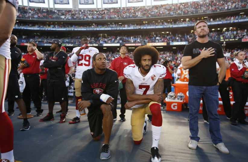 Colin Kaepernick, No. 7, kneels with his teammate Eric Reid during the national anthem prior to a game on Sept. 1, 2016.  (photo credit: MICHAEL ZAGARIS/SAN FRANCISCO 49ERS/GETTY IMAGES)