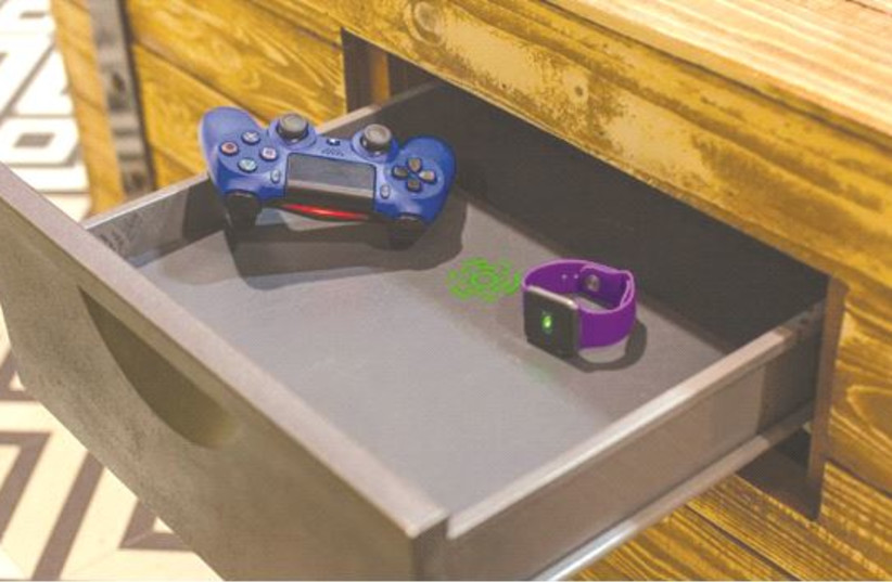 A VIDEO game controller and smart watch charge on a Humovox wireless charging unit. (photo credit: Courtesy)