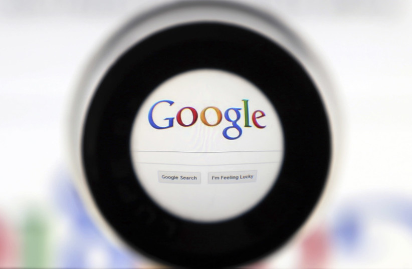 A Google search page is seen through a magnifying glass in this photo illustration taken in Brussels (photo credit: FRANCOIS LENOIR / REUTERS)