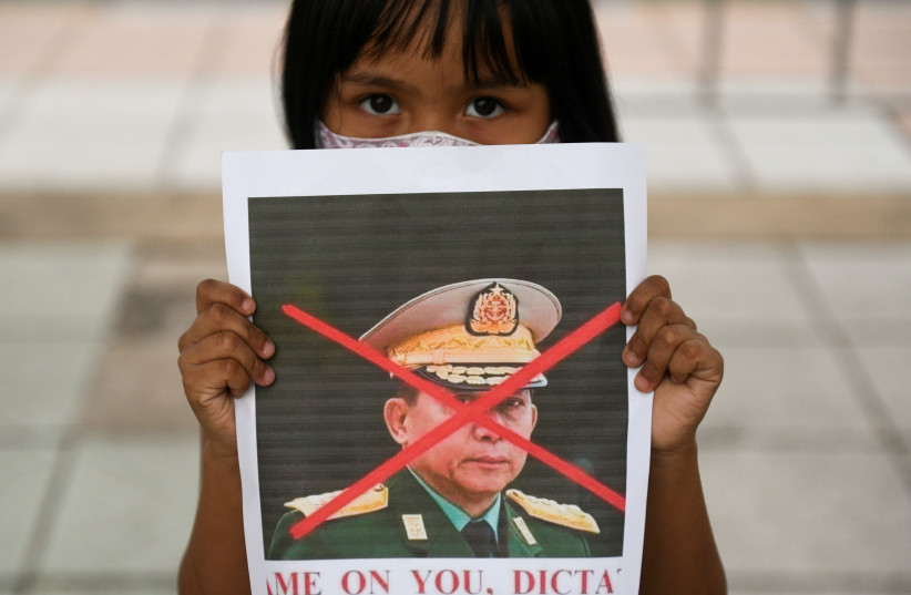 A girl holds a picture of Myanmar's army chief Min Aung Hlaing with his face crossed out as Myanmar citizens protest against the military coup in Myanmar outside United Nations venue in Bangkok, Thailand February 6, 2021.  (photo credit: CHALINEE THIRASUPA/REUTERS)