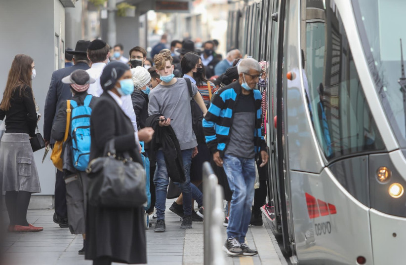 Israelis are seen boarding the light rail on Jaffa Street in Jerusalem after the coronavirus lockdown ends, on February 8, 2021. (photo credit: MARC ISRAEL SELLEM/THE JERUSALEM POST)