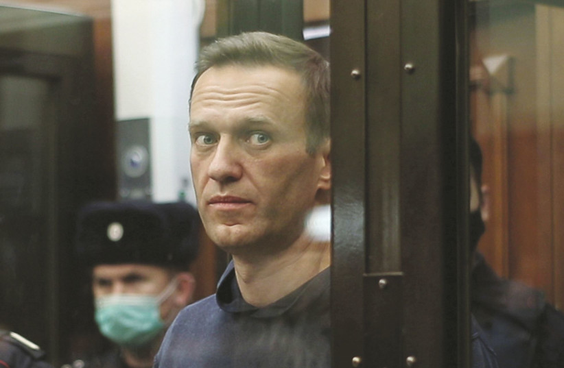 RUSSIAN OPPOSITION leader Alexei Navalny, who is accused of flouting the terms of a suspended sentence for embezzlement, inside a defendant dock during the announcement of a court verdict in Moscow, Russia earlier this month. (photo credit: REUTERS)