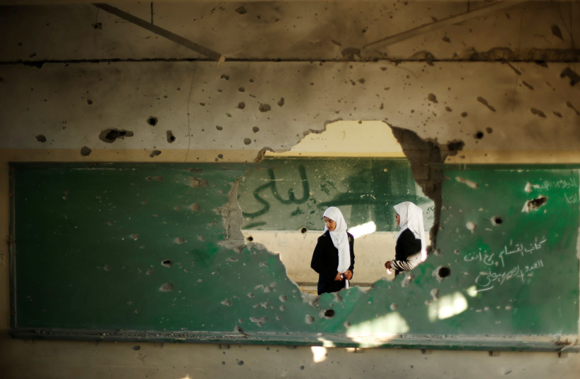 Palestinian students look inside a classroom that witnesses said was shelled by Israel during its offensive, on the first day of the new school year east of Gaza City September 14, 2014. (photo credit: SUHAIB SALEM/REUTERS)
